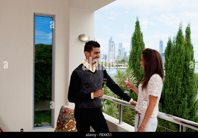 Couple toasting champagne on balcony stock photos couple for Balcony overlooking city