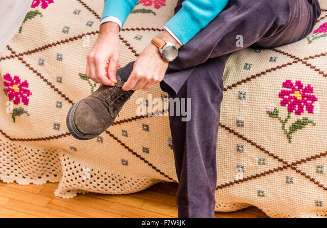 Middle Aged Man Sitting In The Bedroom Ties His Shoelaces   Stock Image