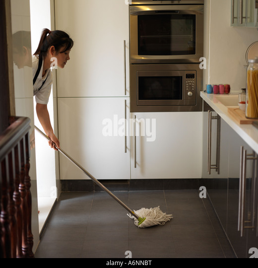 woman cleaning kitchen floor mop stock photos & woman cleaning