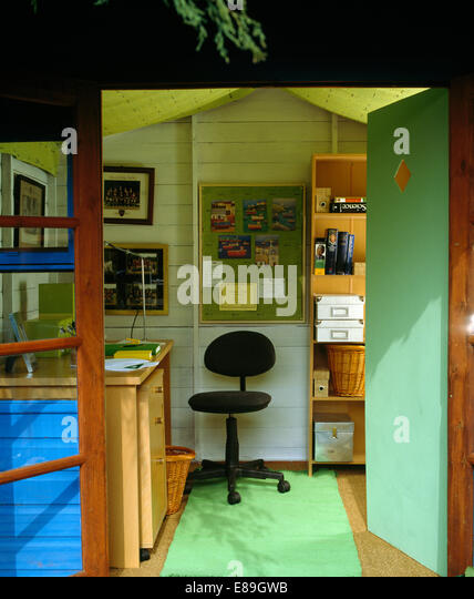 Doors Open To Garden Shed Converted Into Office With Green Rug And Black  Office Chair