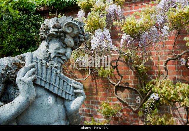 Pan Statue With Wisteria Wall Background At RHS Wisley Gardens, Surrey,  England   Stock