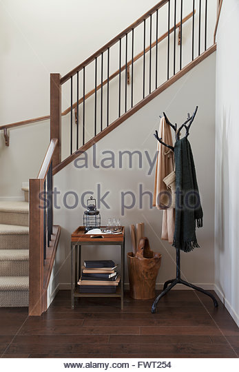 antique coat hook and table by staircase stock image