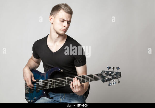 Young Male Musician Playing A Six String Bass Guitar Isolated On Light Background