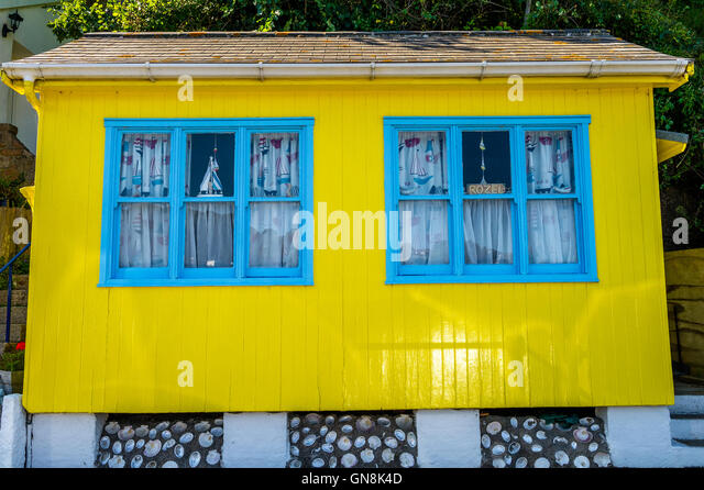 Bright yellow wooden seaside chalet with light blue window frames. - Stock  Image