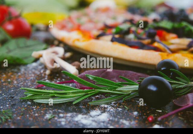 Italian pizza with mozzarella, black olives, prosciutto and tomatoes - Stock Image