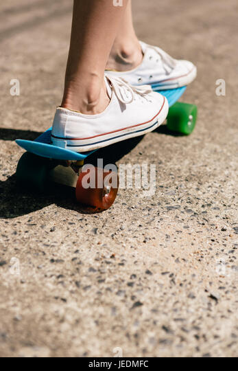 Closeup Of Feet Of A Beautiful Woman In White Trendy Sneakers Rides On Blue  Penny Skate