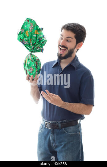Easter egg wrapping paper stock photos easter egg wrapping paper young man presents an easter egg wrapped in green paper celebrating holidays with gifts and negle Gallery