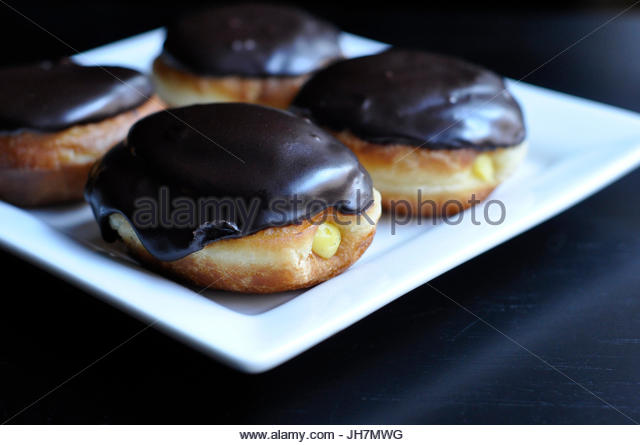 Vanilla cream filled doughnuts with chocolate glaze on a white square plate. - Stock Image
