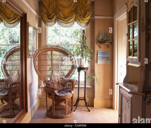 Wicker Peacock Chair Against Window With Festoon Blind On Nineties Landing    Stock Image