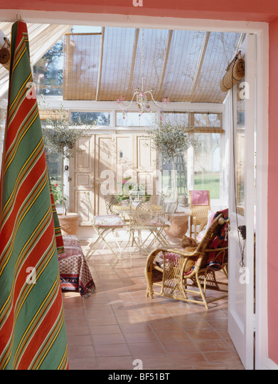 Door Open To Conservatory Dining Room With Split Cane Blinds And Wooden Flooring