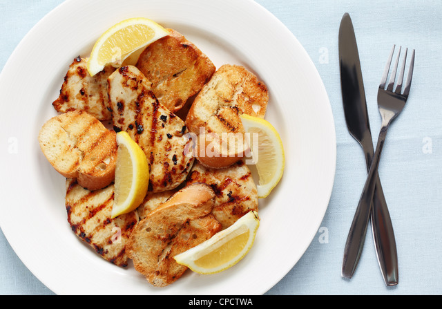 Grilled lemon chicken with garlic bread - Stock Image