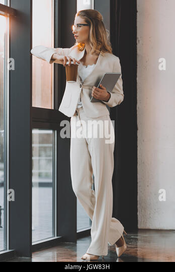 attractive pensive businesswoman in white suit with digital tablet and coffee standing at window in office - Stock Image