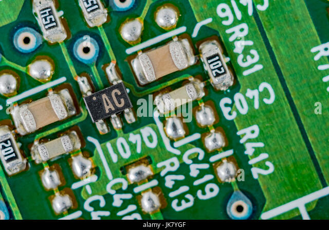 Surface mount technology (SMT) components on a green printed circuit board. Wiring inside computer. - Stock Image