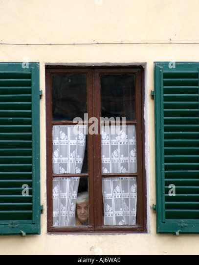 elderly woman peeking out window italy stock image