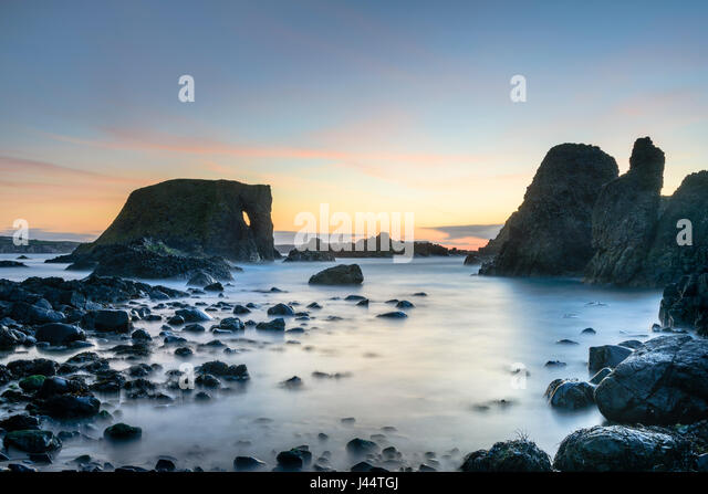 Sunset at Elephant Rock at Carricknaford a coastal scene of rocky shore near Ballintoy and Whitepark Bay on the - Stock Image