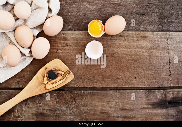 Farm fresh organic brown chicken eggs from free range chickens with an old olive wood antique spatula over a rustic - Stock Image