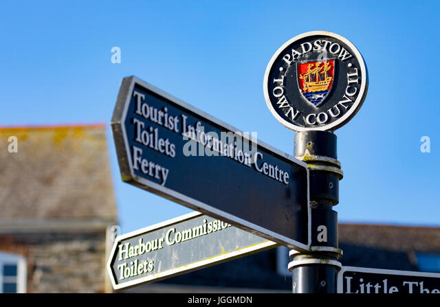 A Padstow Town Council cast iron tourism information sign with crest pointing in different directions agains a clear - Stock Image
