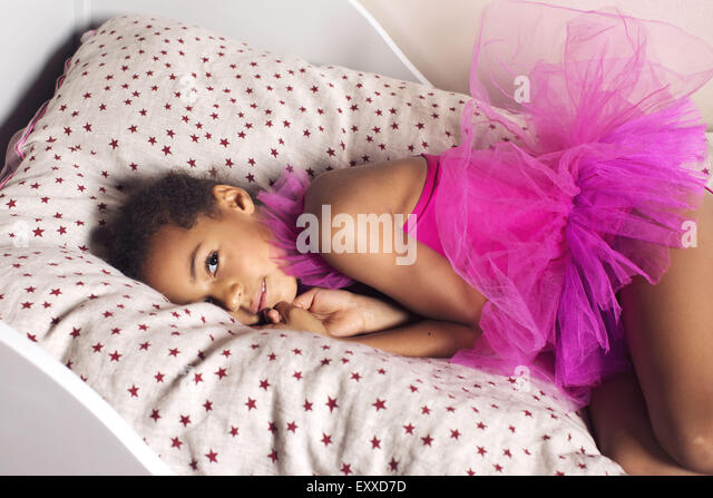Girl lying on bed in tutu - Stock Image