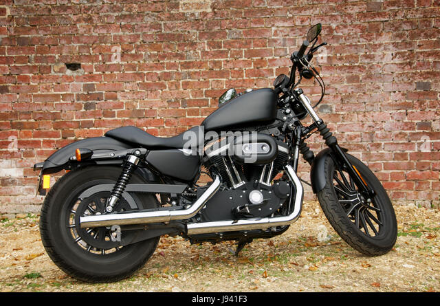 Black Harley Davidson Iron 883 Motorcycle Against A Brick Wall