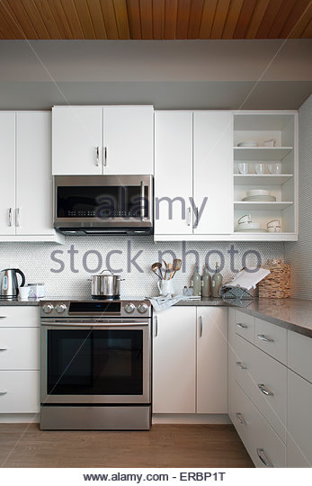 Modern White Kitchen With Stainless Steel Appliances Stock Image