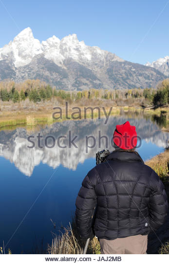 Just after sunrise a photographer surveys the Teton Range and Snake River in Grand Teton National Park. - Stock Image