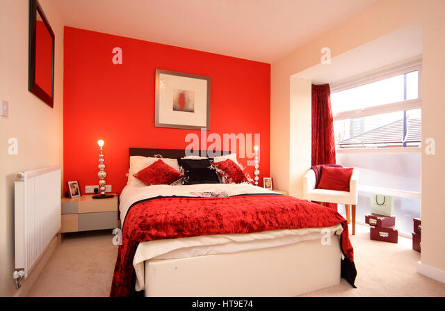 Home interior  bedroom in bright red  feature wall  bed throw  curtains. Home Interior Bedroom Bright Red Stock Photos   Home Interior