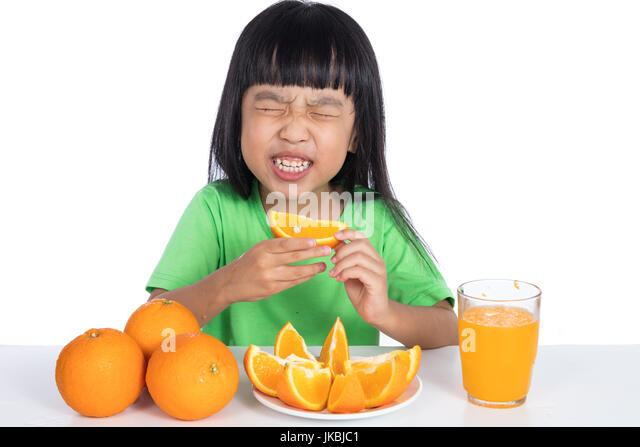 Asian Chinese little girl eating sour orange and making grimace in isolated white background - Stock Image