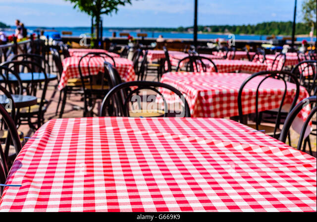 Red And White Checkered Table Cloths At An Outdoor Eatery With Coastline In  Background. Copy