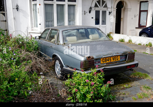 An old Jaguar XJ6, abandoned and rusting in a driveway in Clacton, Essex - Stock Image