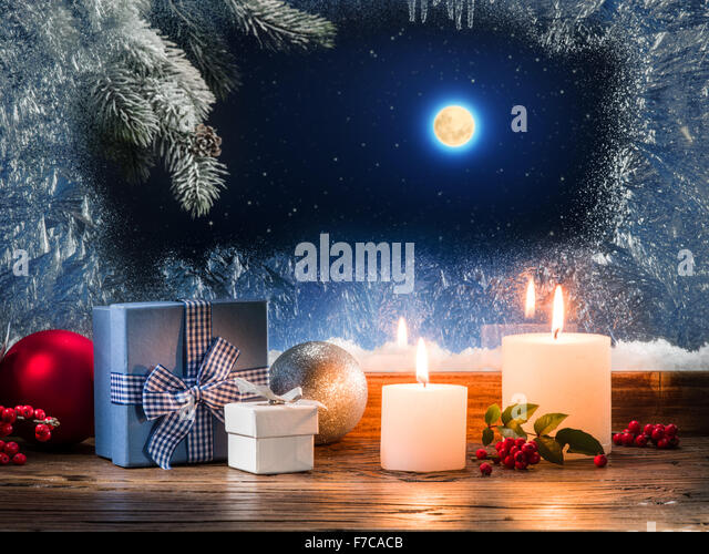 christmas presents with burning candle on the windowsill with pattern frost stock image