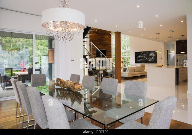 modern interior design luxury open plan dining room with glass dining table and grey upholstered dining