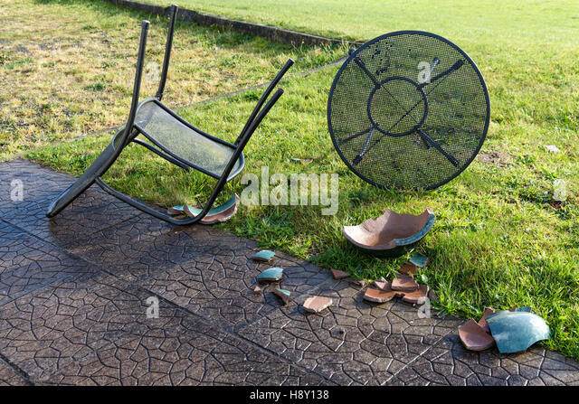 blown over garden table and chairs and broken ceramic plant pot caused by high winds