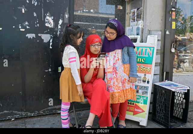 Three young girls checking out a cell phone while their parents were shopping on 37th Avenue in Jackson Heights, - Stock Image