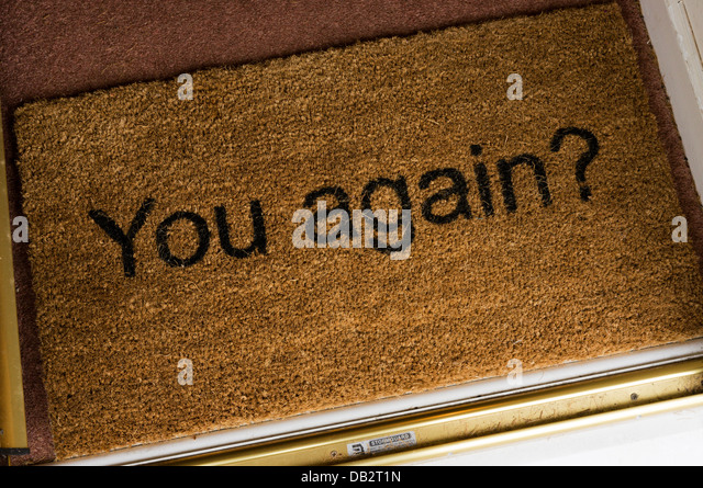 a jokey doormat inside the front door of a house stock image