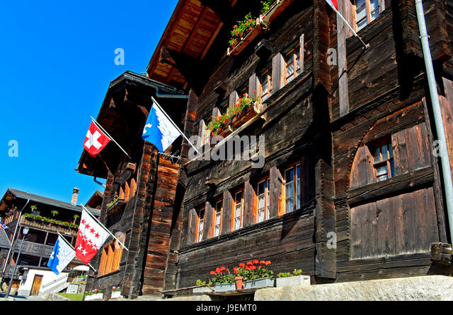 Swiss chalet with flags of the country, the canton and the municipality, Blatten, Lötschental, Valais, Switzerland - Stock Image