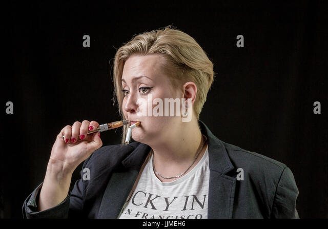 Girl tries to smoke new modern electronic cigarette - Stock Image