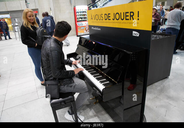 Man playing a piano in a public space, Roissy Charles de Gaulle airport, Paris, France - Stock Image