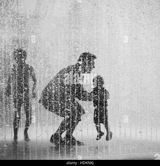 Silhouette Of A Young Boy Man And Toddler Playing In Water Fountain