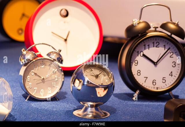a lot of various alarm clock on blue carpet stock image