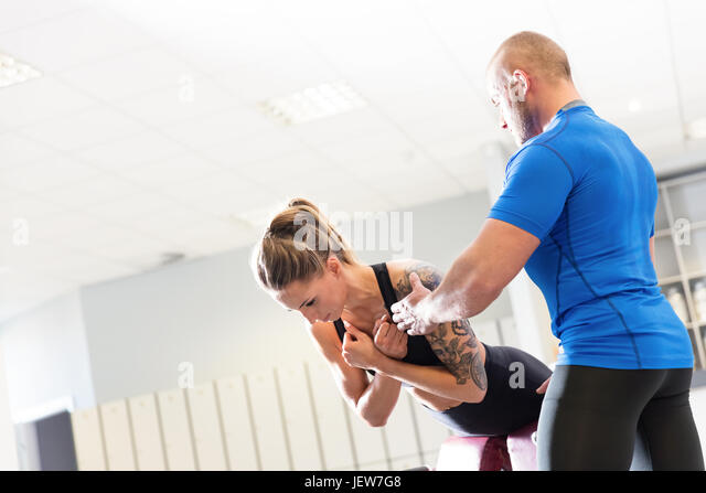 Personal trainer working with a client at the gym. Workout assistance and motivation. Sport concept. - Stock Image