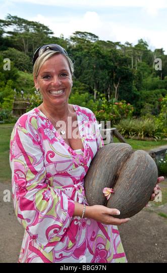 a woman holding a coco de mer le jardin du roi spice garden mahe - Rosa Krbislampe