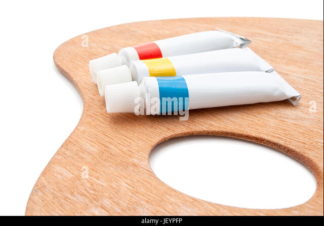 A Traditional Wooden Artists Palette With Tubes Of Paint In Primary Colours Isolated On White