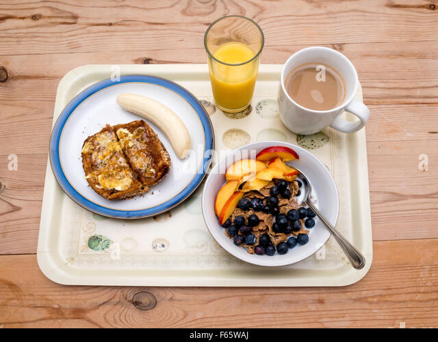 a breakfast tray cereal bran flakes with blueberries and nectarine f65waj Orange Coffee Table Heart Shaped Fried Eggs Bread And Orange Juice Stock Photo Image