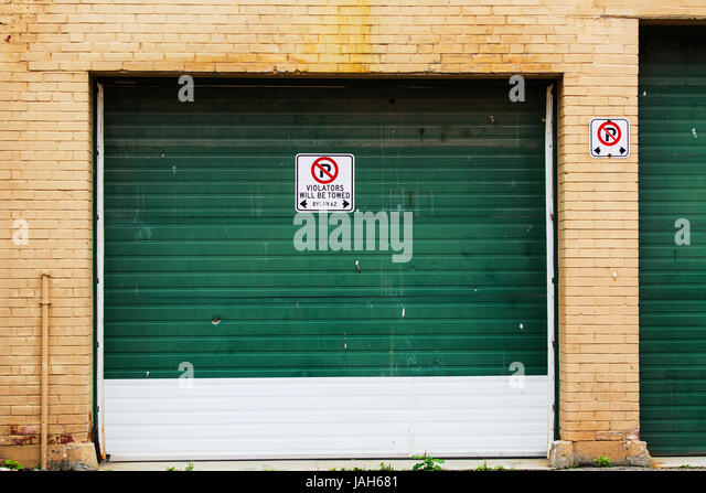 industrial roll up garage door with no parking sign stock image