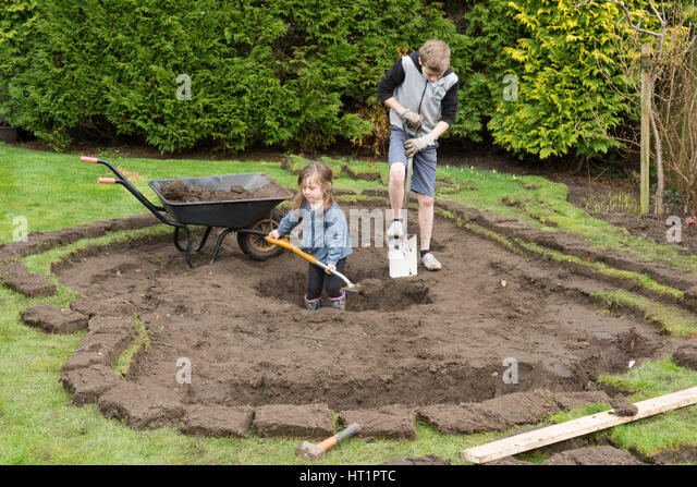 Children digging hole stock photos children digging hole for Digging a garden pond