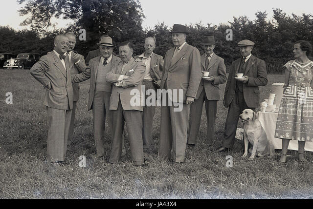 1950s, historical. group of well dressed gentlemen stand together having a cup of tea at a fete or outdoor event. - Stock Image
