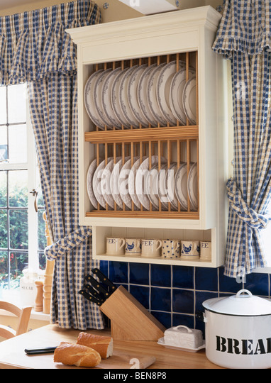 Close Up Of Cream Plate Rack Between Windows With Blue Checked Curtains In Country