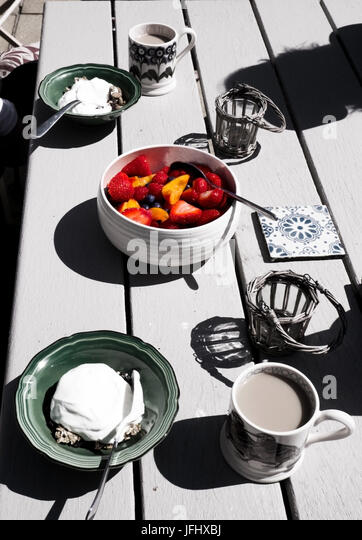 a white wooden table top with a healthy breakfast on it in the middle a brightly coloured bowl of fruit with strawberries, - Stock Image