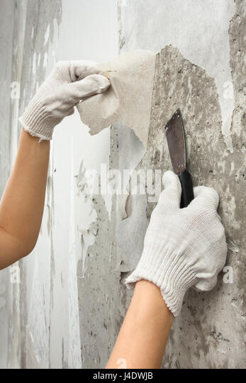 Hands Removing Old Wallpaper From Wall With Spatula