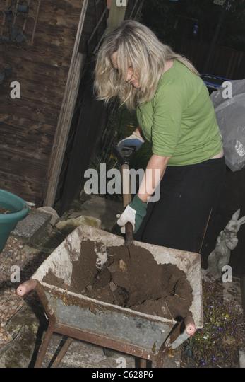 Wheelbarrow with gravel stock photos wheelbarrow with for Soil 7t7 woman